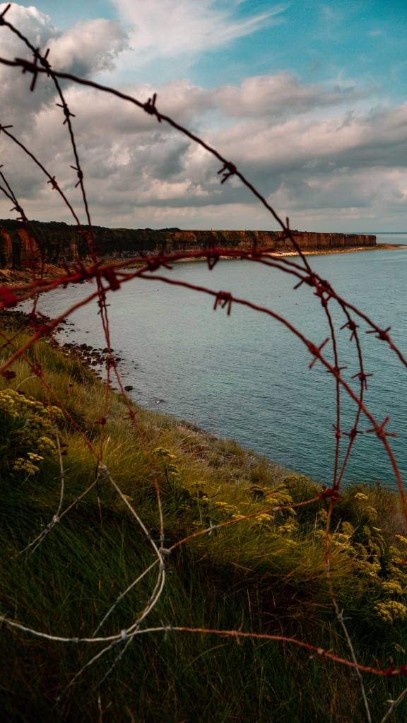 A view of the cliffs west of point du hoc looking through aged rusty barbed wire.
